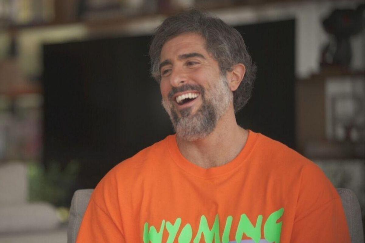 Marcos Mion sorrindo durante entrevista para o Fantástico