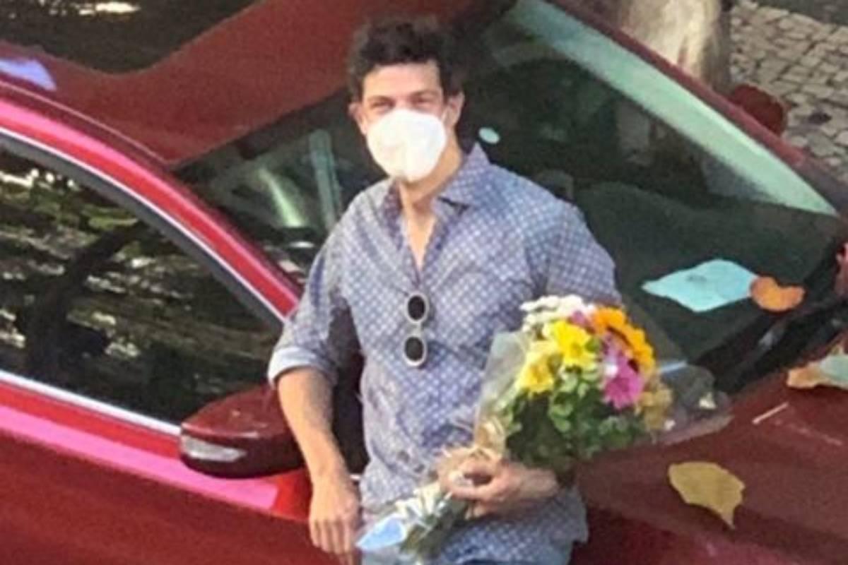 mateus solano carregando buquê de flores perto de carro