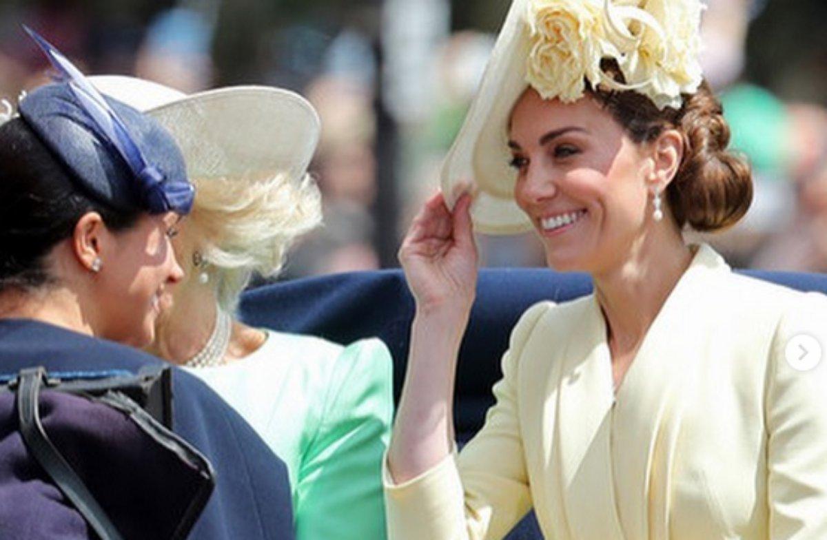 Meghan Markle e Kate Middleton sorridentes em carruagem