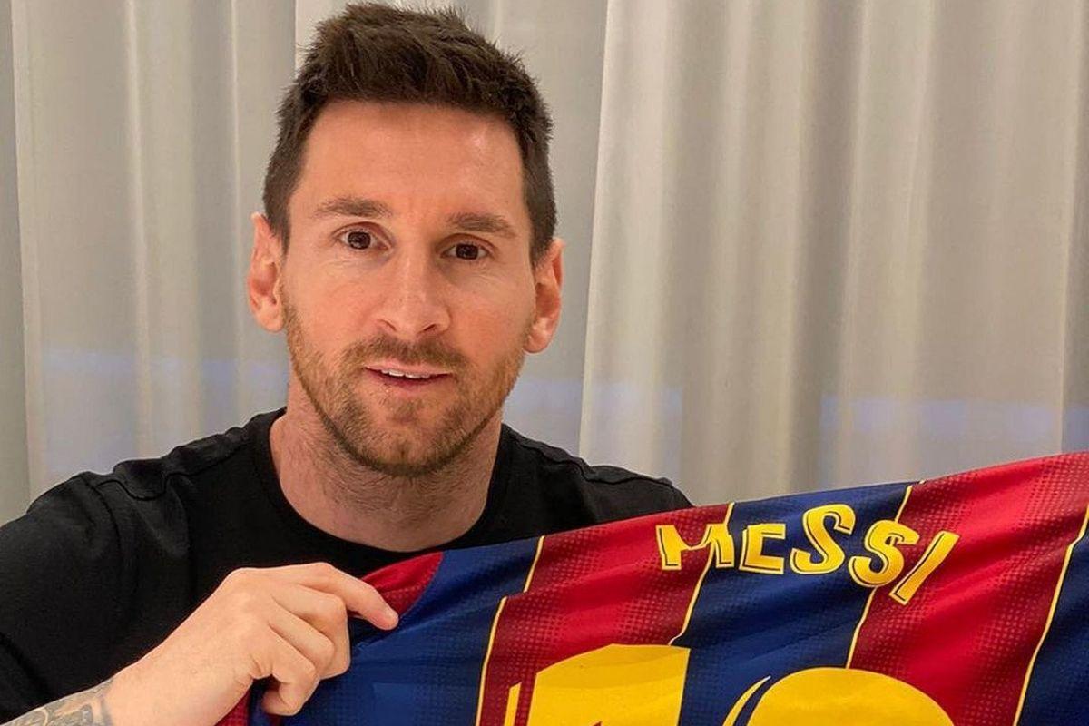 Foto de Lionel Messi sorrindo e segurando uma camiseta do Barcelona