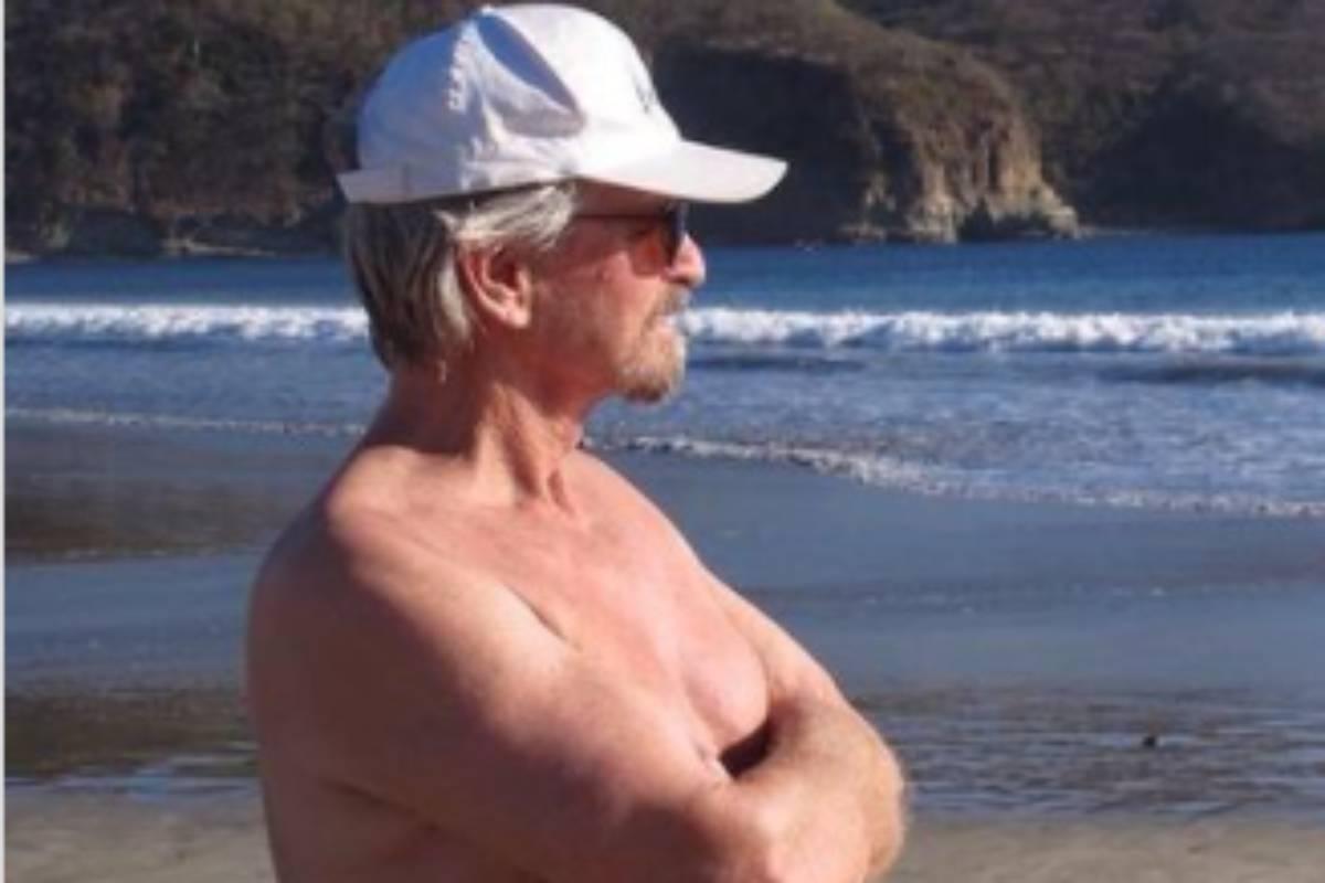 michael douglas sem camisa em praia admirando o mar