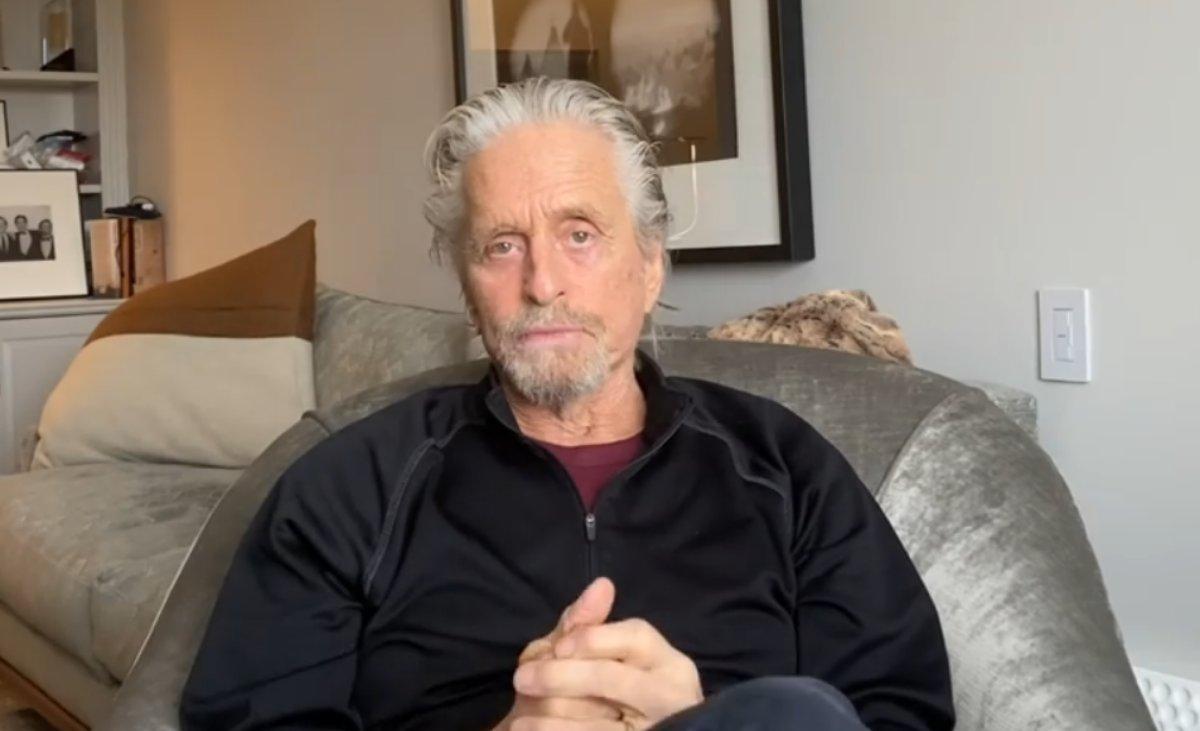 Michael Douglas fala no sofá de sua casa