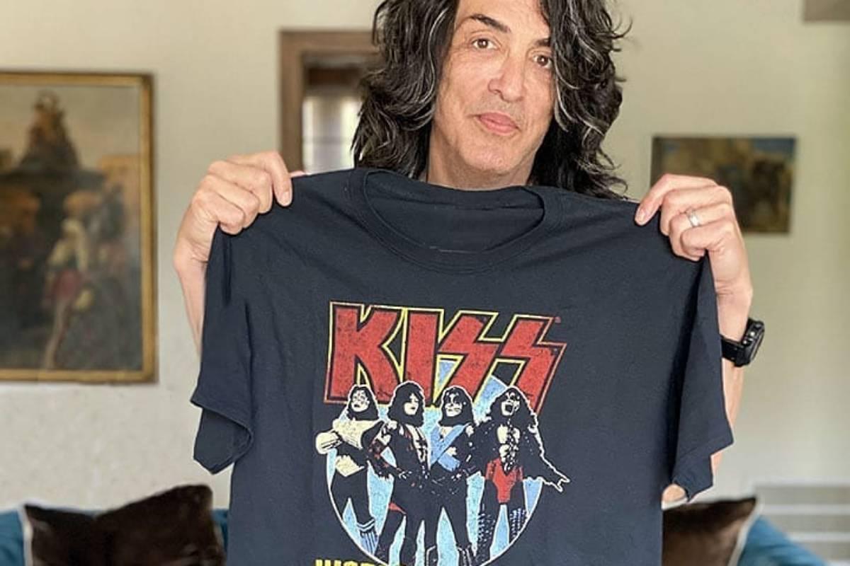 paul stanley segurando e mostrando camiseta com estampa da banda kiss