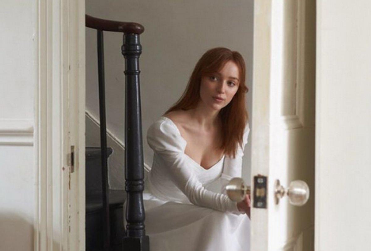 Phoebe Dynevor sentada em escada para anuncio