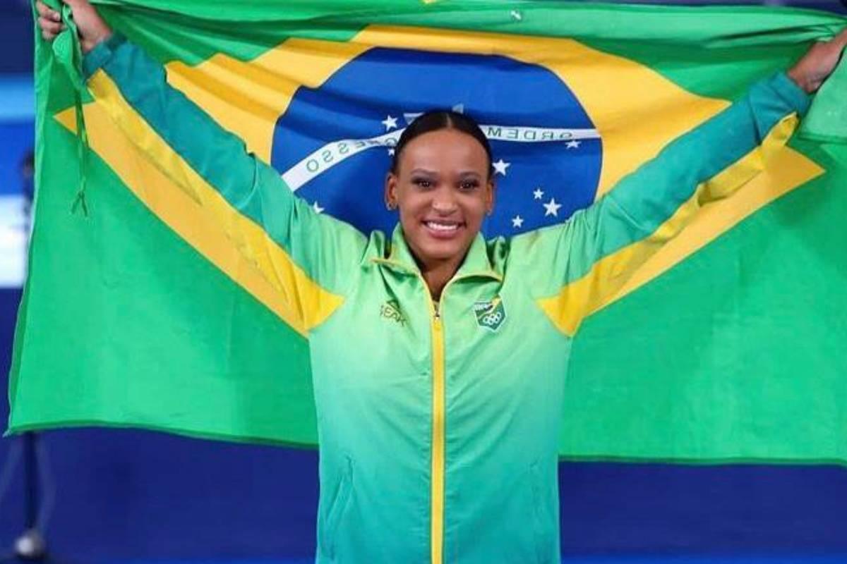 rebeca andrade com a bandeira do brasil em pódio de tóquio