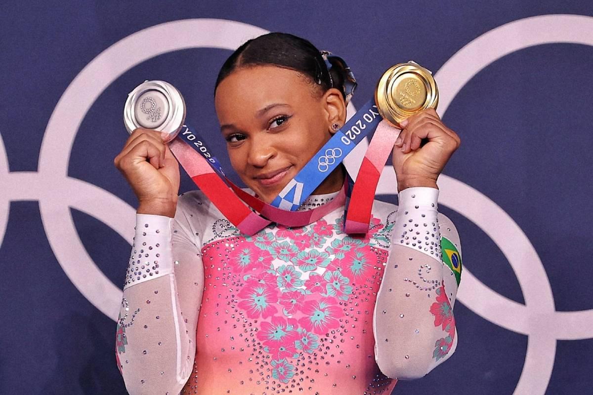 rebeca andrade segurando medalhas de ouro e prata