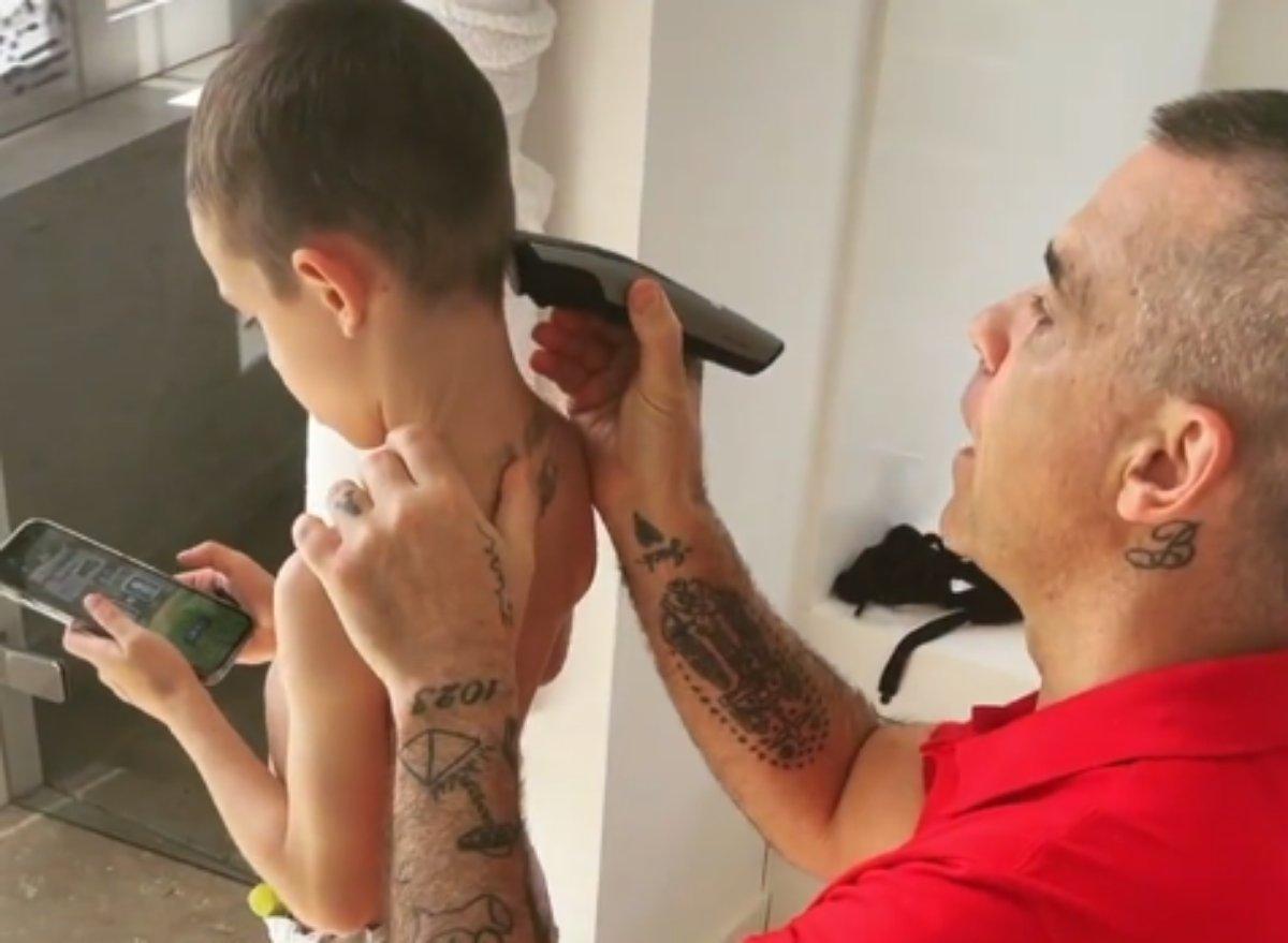 Robbie Williams corta o cabelo do filho