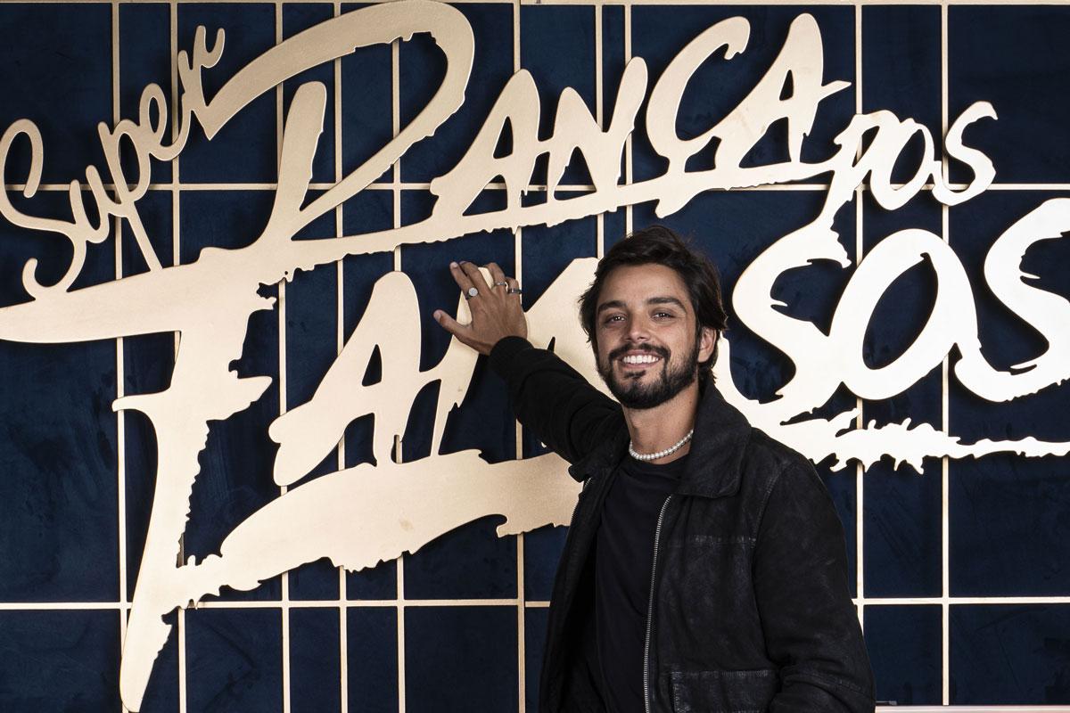 Rodrigo Simas sorrindo com a logo do Super Dança dos Famosos atrás