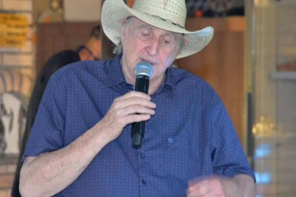sérgio reis com microfone em mãos e próximo da boca usando um chapéu de palha