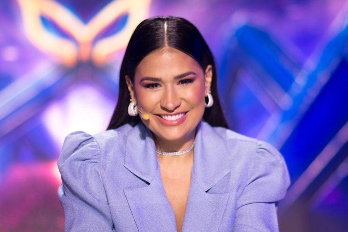 Simone Mendes sorrindo, com o cabelo repartido ao meio, roupa roxa e o microfone portátil perto da boca
