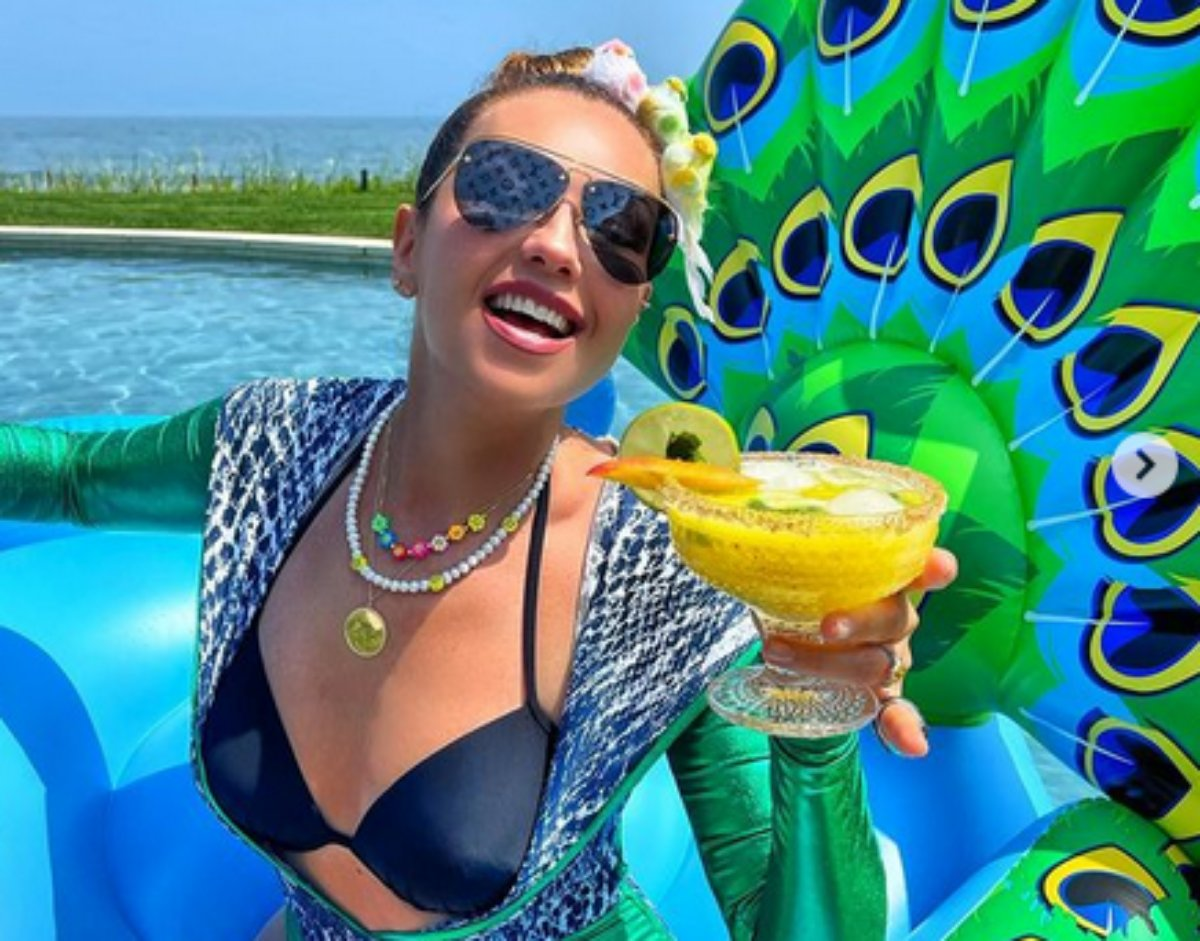 Thalía posa na piscina com uma bebida na mão