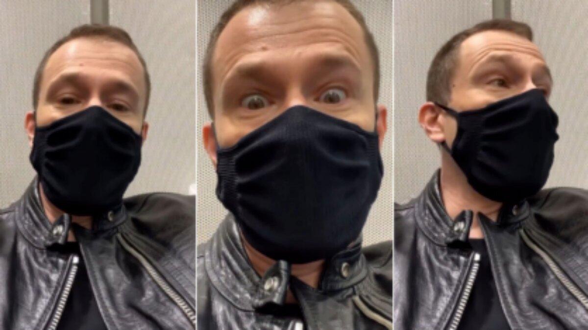 Tiago Leifert de jaqueta de couro preta e máscara de proteção preta