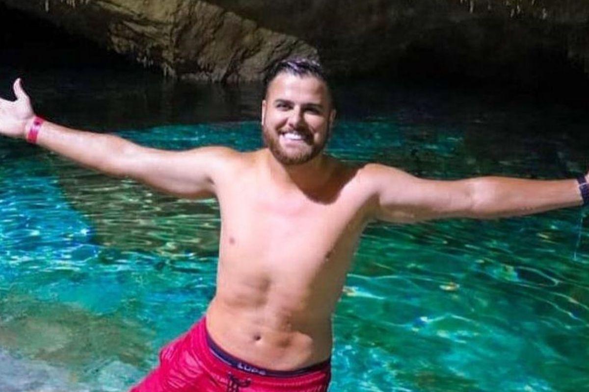 Zé Neto de braços abertos, sem camisa, sorrindo e vestindo bermuda vermelha em lagoa cavernosa