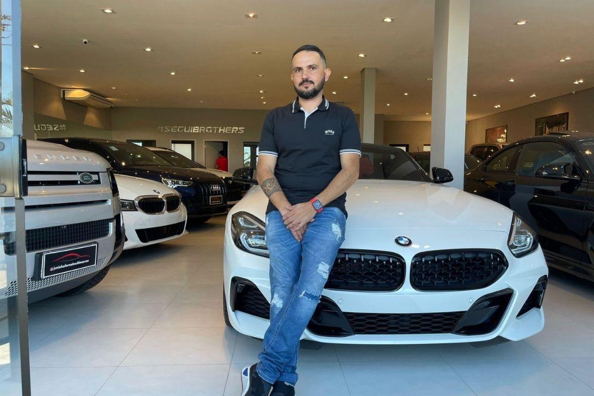 Juninho Fornel posando com carros de luxo