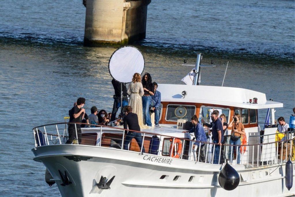Cercada por uma equipe de produção enorme, Julia Roberts desce o rio Sena, em Paris.