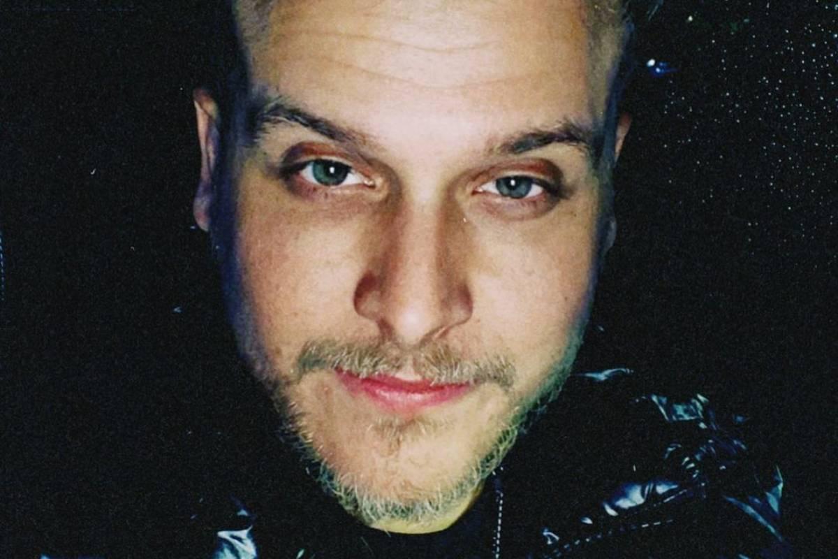 rosto de Bruno Martini em foco ao posar em fundo preto brilhante
