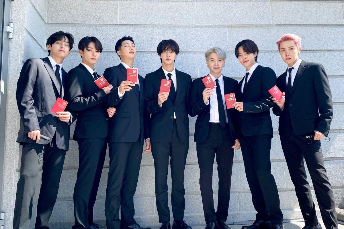 Foto dos meninos do BTS vestido com ternos pretos, lado a lado, olhando para a câmera e segurando os passaportes diplomáticos