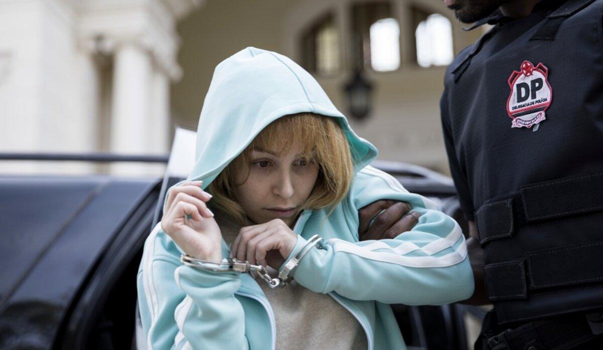Carla Dias caracterizada como Suzane Von Richthofen, de casaco azul claro, de capuz, segurada por policiais