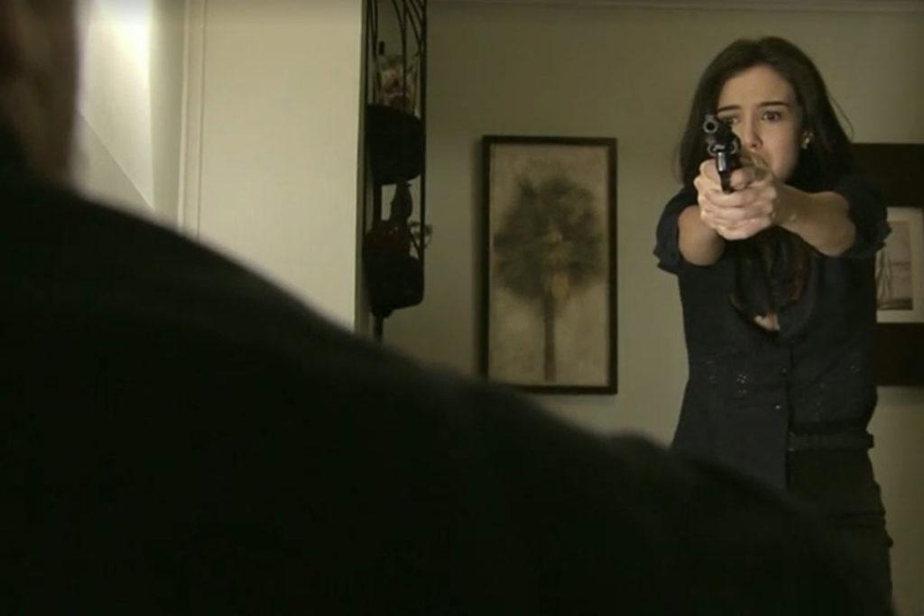 Cora aponta uma arma para Reginaldo