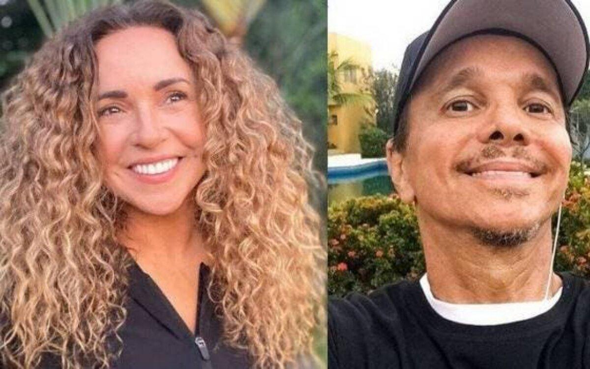 Daniela Mercury sorrindo, de camisa preta, Netinho de boné e camisa preta, sorrindo