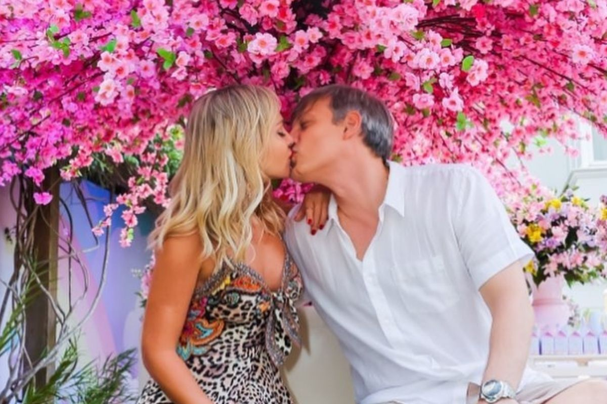 Eliana beijando o marido sob uma árvore de flores cor de rosa