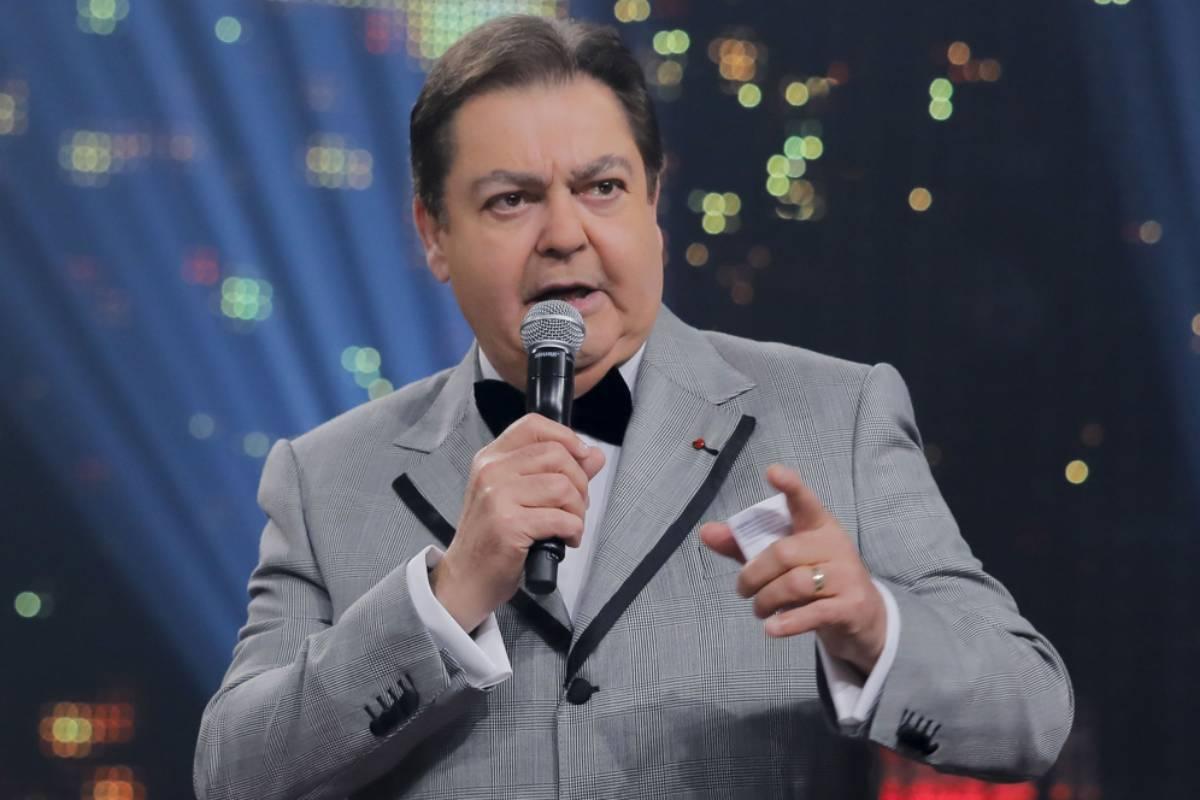faustão de terno cinza de microfone apresentando os melhores do ano de 2018