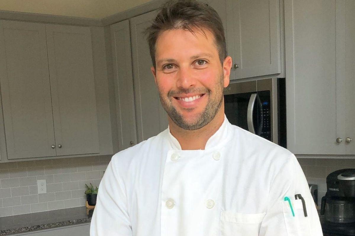 Gustavo Leão sorrindo, com dolmã de cozinheiro