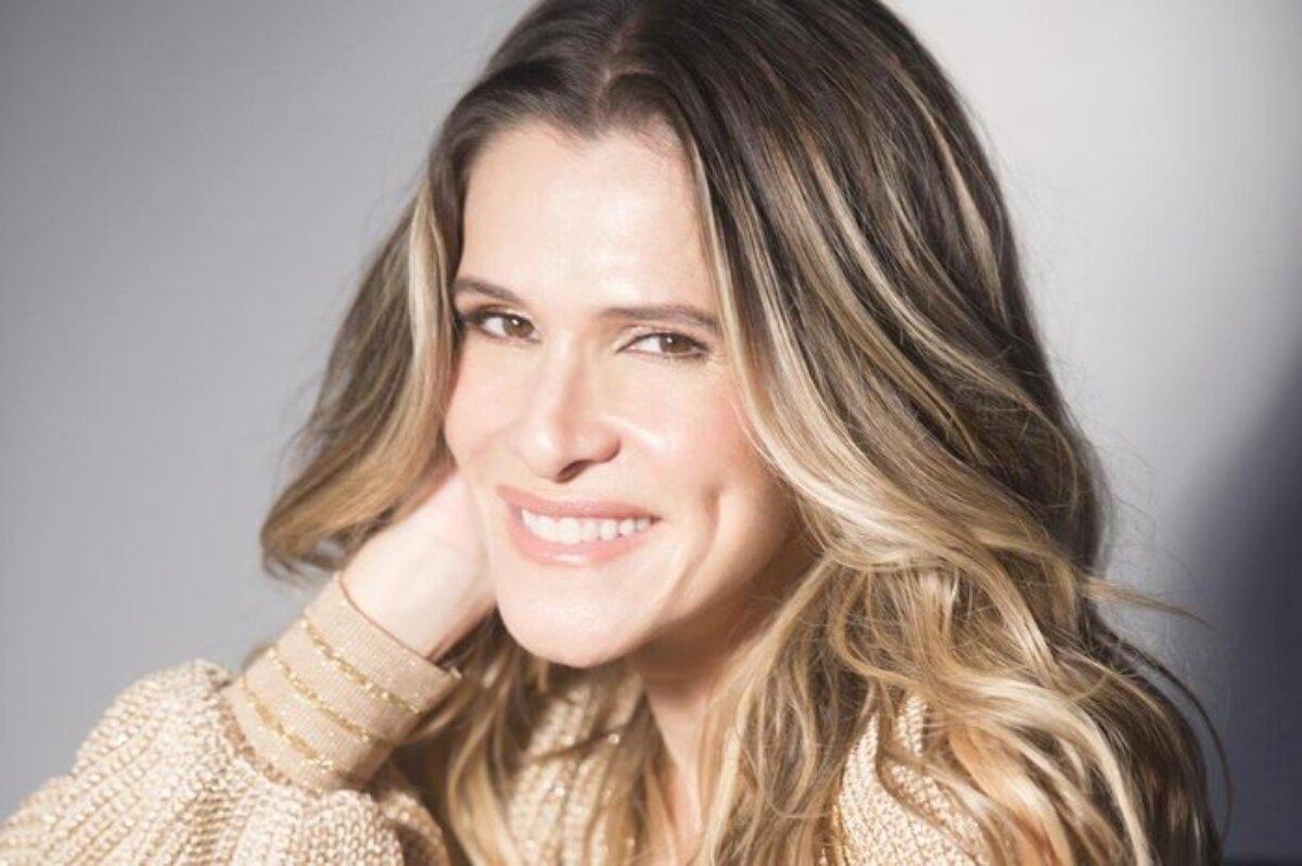 Ingrid Guimarães sorrindo, com a mão esquerda no pescoço