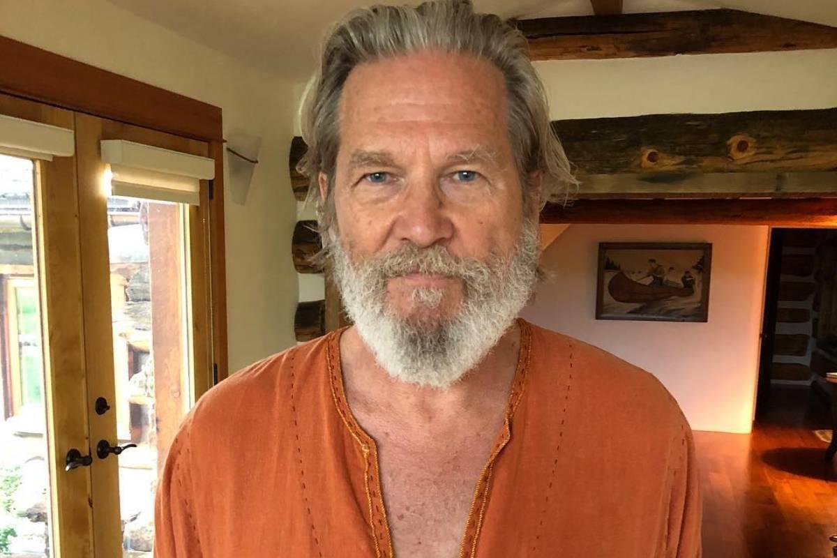 jeff bridges posando de roupa laranja e barba grande