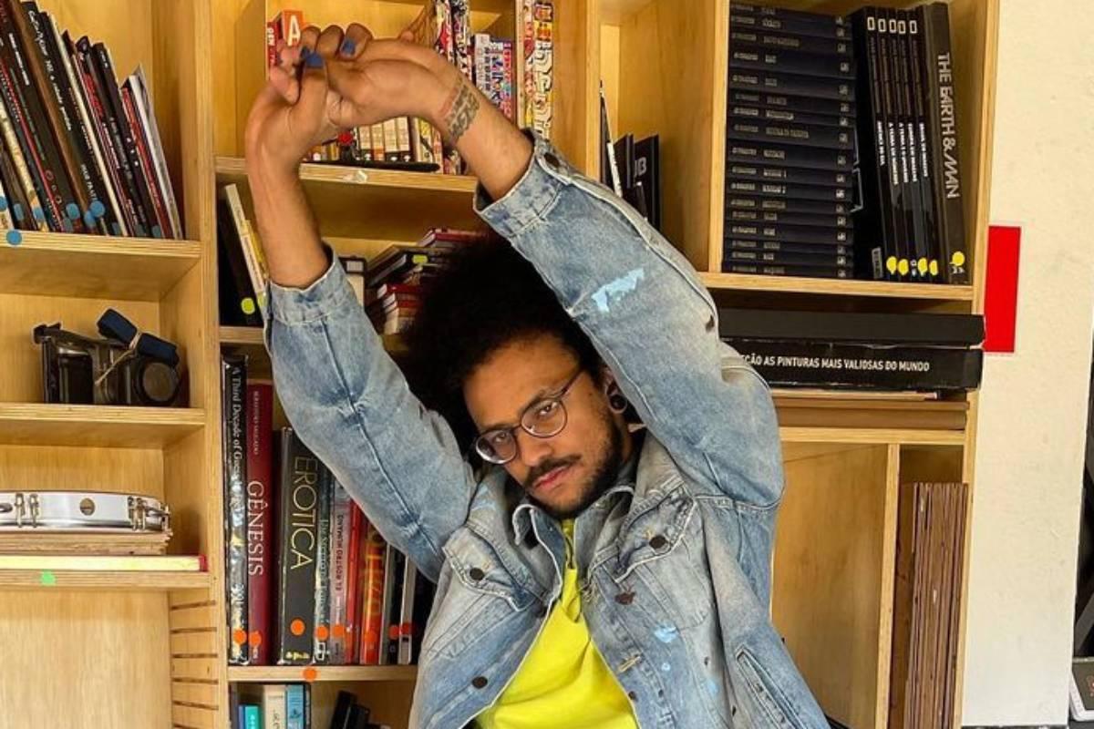 joão luiz pedrosa se espreguiçando em frente a estante com livros