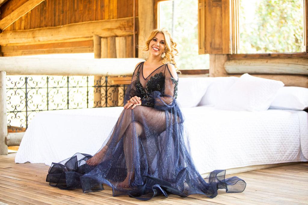 Joelma com vestido com detalhes transparentes, sentada em cama
