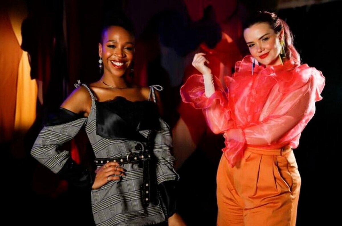 Karol Conká de vestido conza e detalhes pretos, com a mão direita na cintura, ao laod de Marcela Mc Gowan, de calça laranja e blusa vermelha