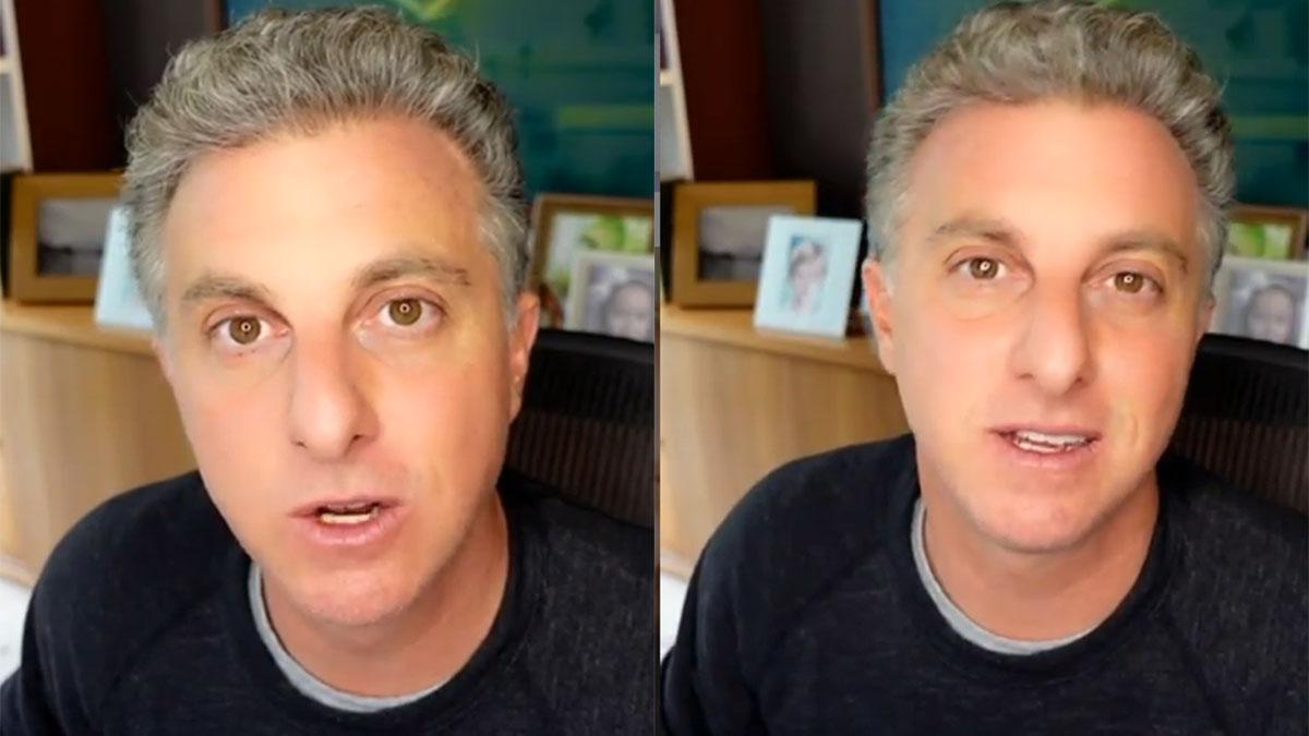 Luciano Huck, falando para a câmera, sentado no escritório, de camiseta preta