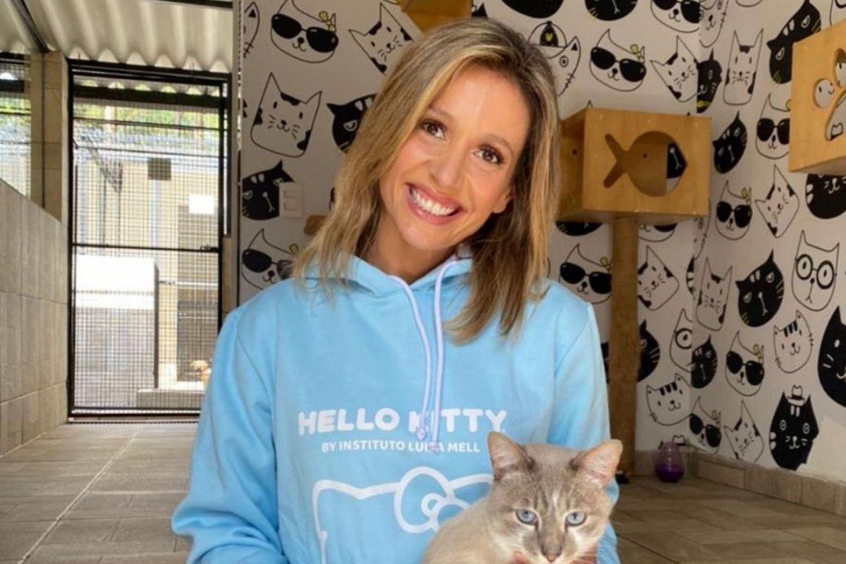 Luisa Mell de blusa azul e sorridente