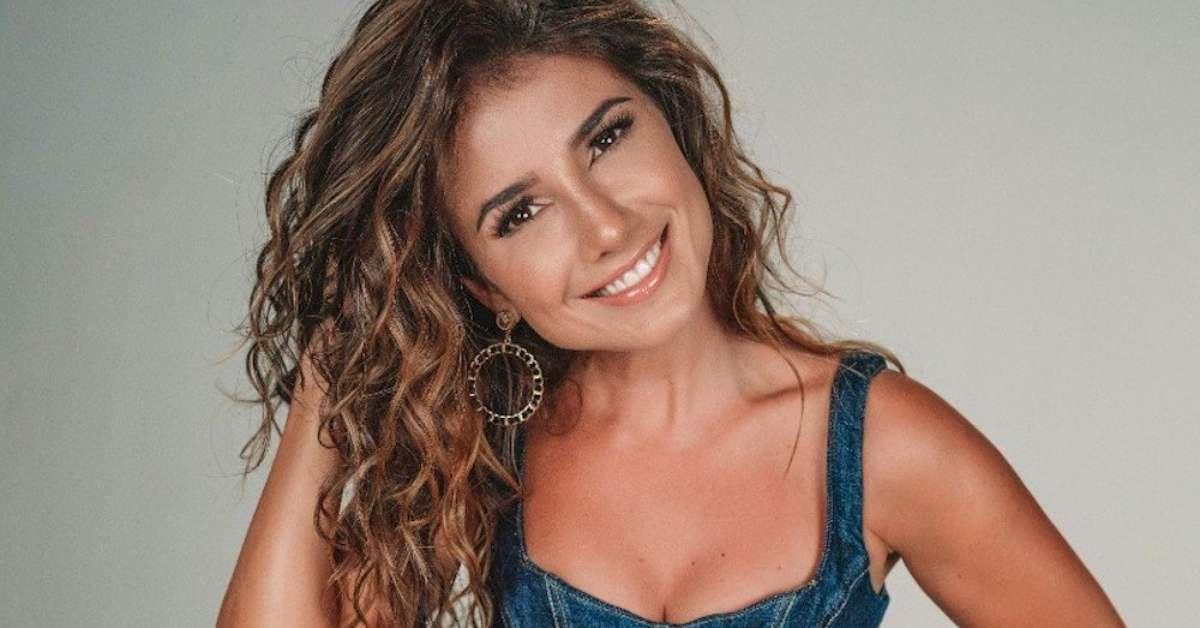 Paula Fernandes de blusa jeans, com a mão nos cabelos, sorrindo
