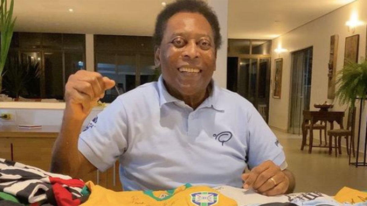 Pelé, sentado na sala, com camisetas oficiais de time