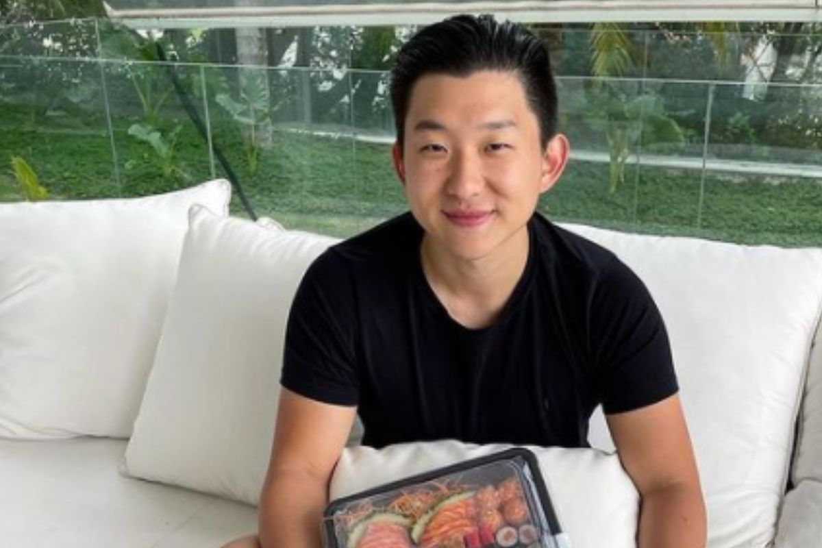 Pyong Lee sentado na cama