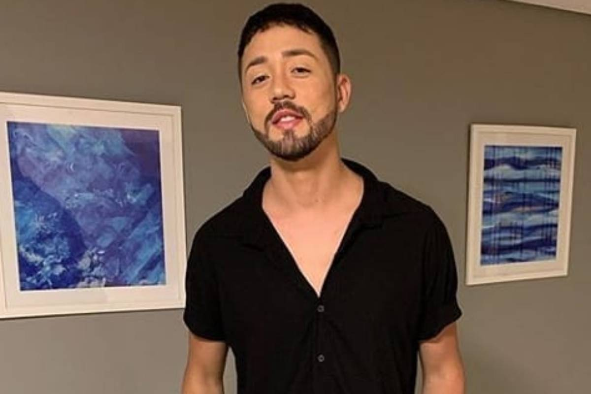 rico melquiades de camisa preta posando entre dois quadros azuis