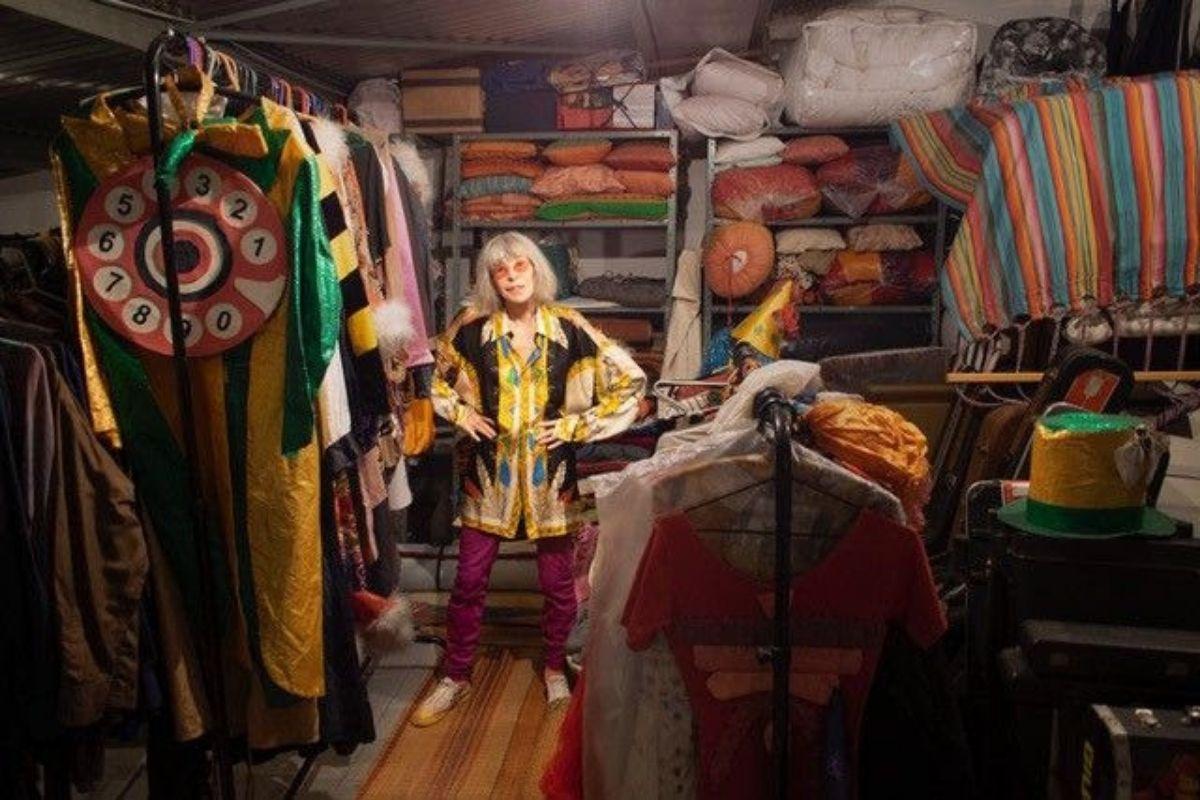 Rita Lee posa em sala com alguns de seus acervos