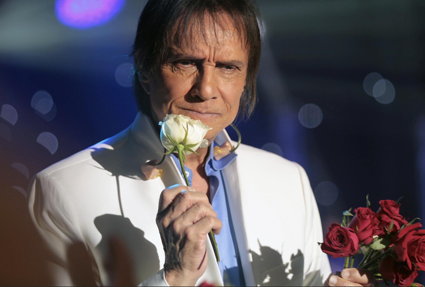 Roberto Carlos beijando rosa no palco