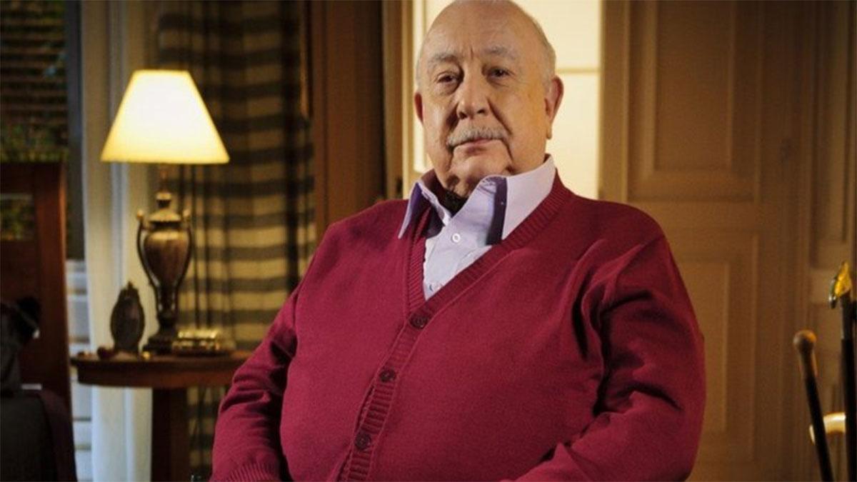 Sérgio Mamberti sentado, de blusa vermelha