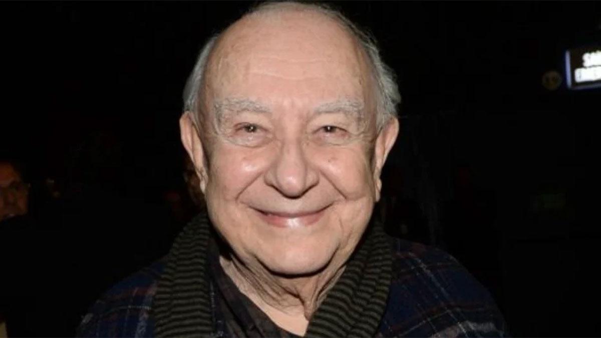 Sérgio Mamberti em plateia de teatro, sorridente