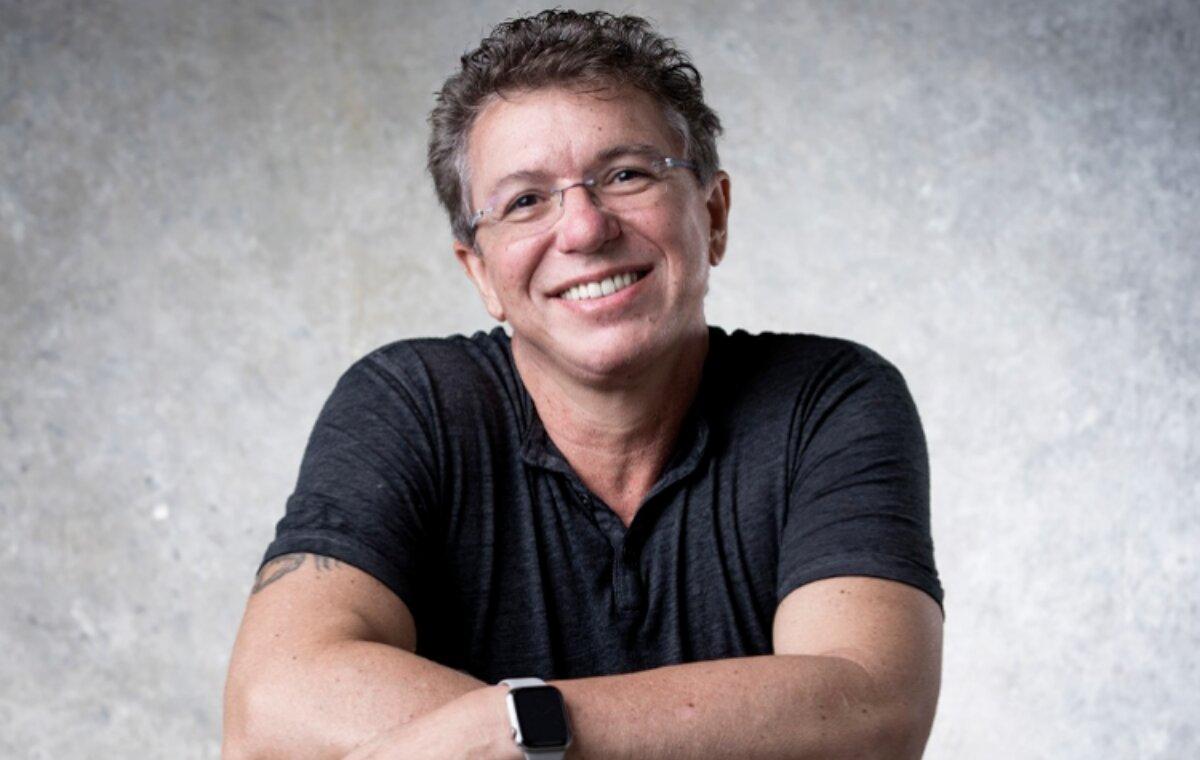 Boninho sorrindo, de braços cruzados, camisa preta