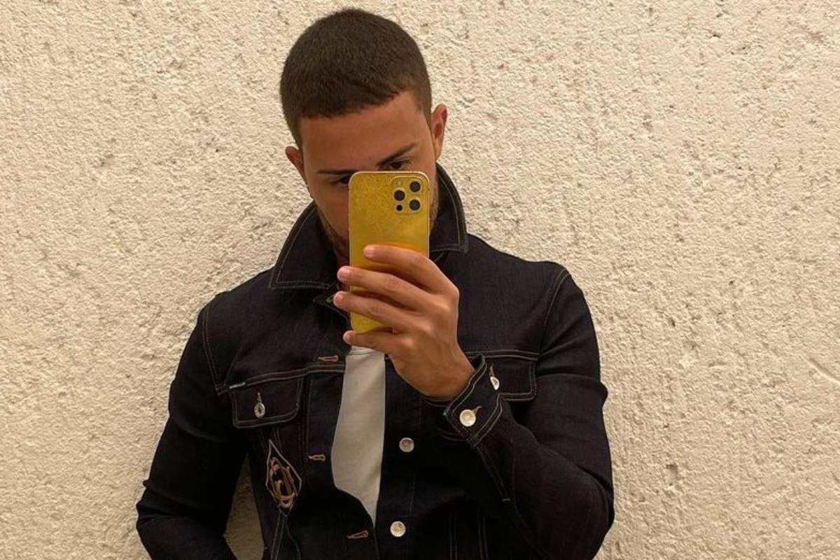 carlinhos maia tirando selfie com celular amarelo e usando jaqueta jeans preta