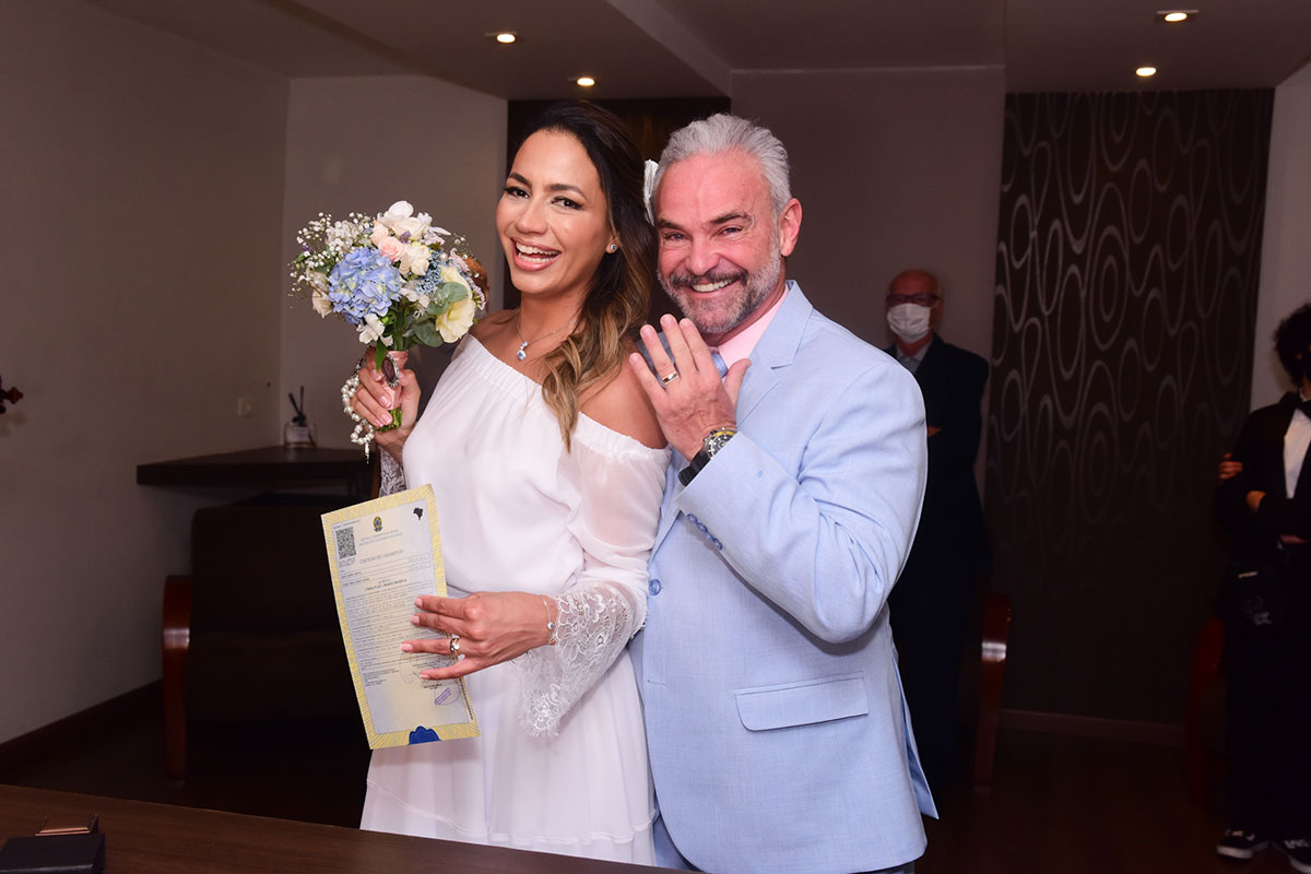 Os noivos mostram alianças e certidão de casamento