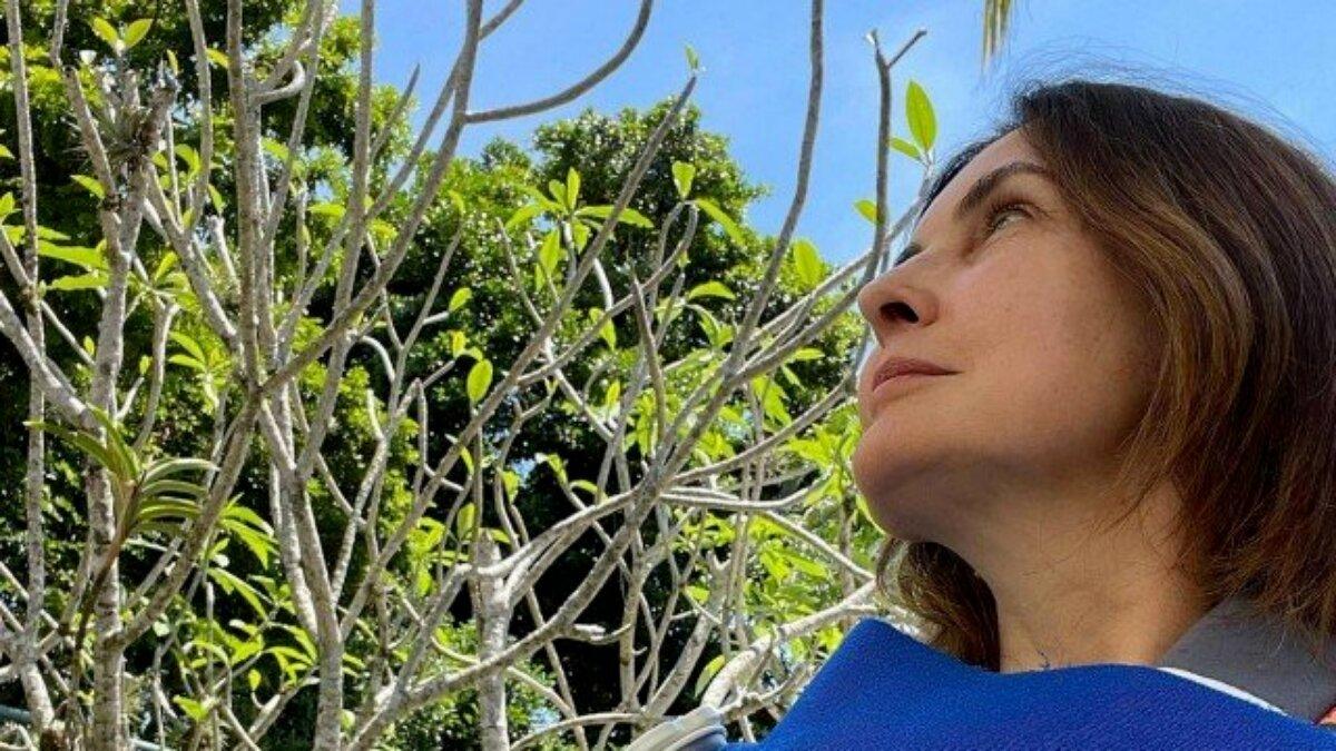 Fátima Bernardes observa a natureza de blusa azul e tipóia