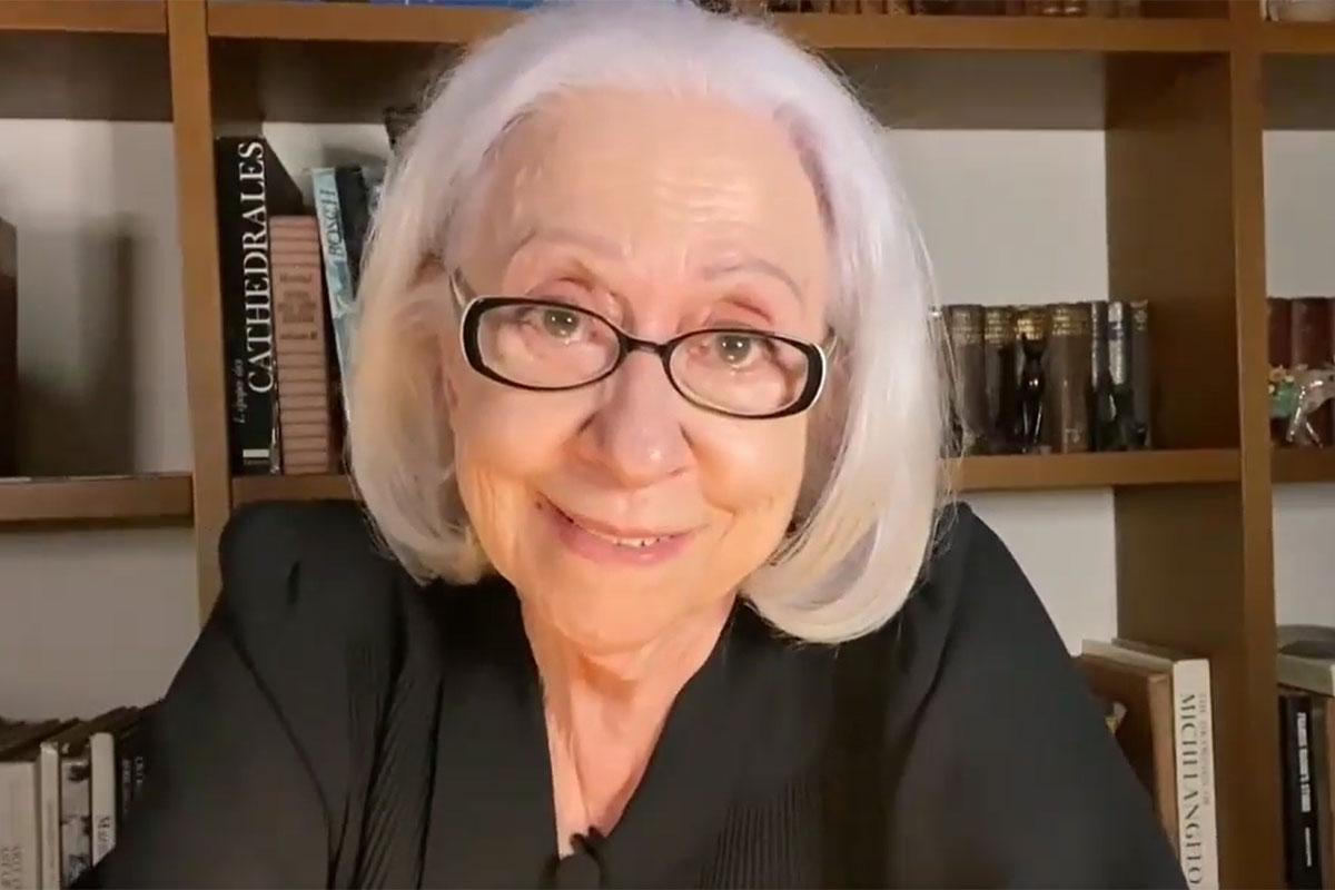 Fernanda Montenegro sorridente, de óculos, em seu escritório
