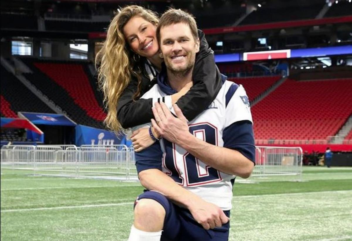 Gisele Bundchen abraçada ao marido, Tom Brady, no campo de futebol americano