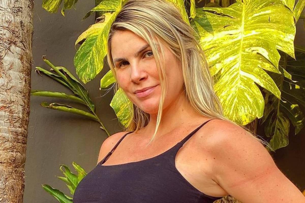 julia faria posando sorrindo de top preto em local com natureza ao fundo