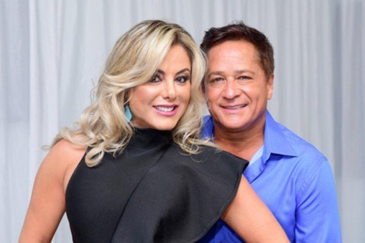 Poliana Costa, de vestido preto, abraçada ao marido, Leonardo, que veste camisa social azul